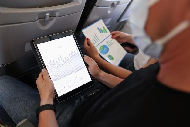 L'uomo e la donna stanno volando in aereo indossando maschere protettive con tablet digitale e documenti in primo piano nelle loro mani