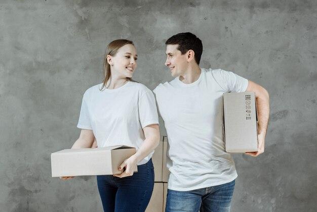 Un uomo e una donna tengono delle scatole di cortone nella casa acquistata.