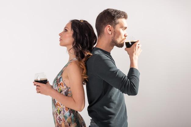 L'uomo e la donna stanno tenendo bicchieri di birra scura sul muro bianco con spazio di copia. concetto di oktoberfest.