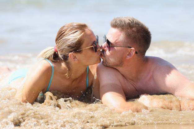 L'uomo e la donna sono sdraiati sulla spiaggia e si baciano
