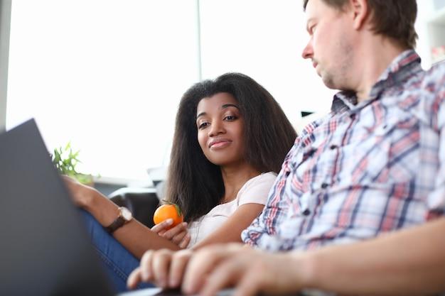 Un uomo e una donna sono seduti sul divano con il laptop