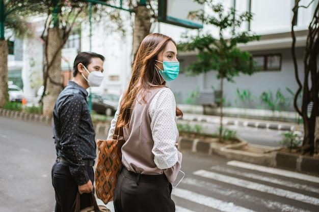 L'uomo e la donna stanno camminando attraversando la strada indossando la maschera