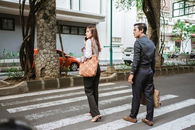 L'uomo e la donna stanno camminando attraversando la strada