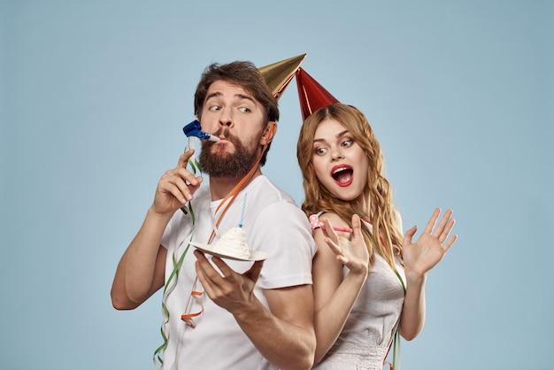 Un uomo e una donna per un compleanno con un cupcake e una candela in un berretto festivo si divertono e celebrano la vacanza insieme, coppia felice