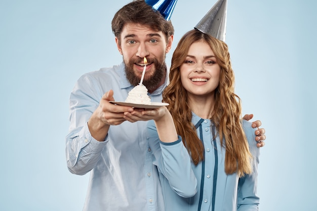 Un uomo e una donna per un compleanno con un cupcake e una candela in un berretto festivo si divertono e festeggiano insieme la festa