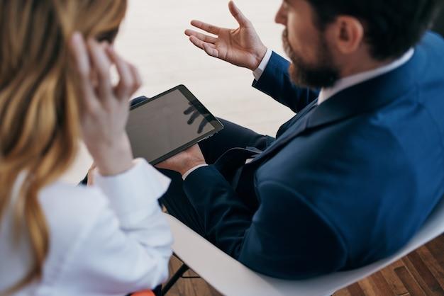 Uomo e donna in giacca e cravatta che guardano l'ufficio della tecnologia dei tablet