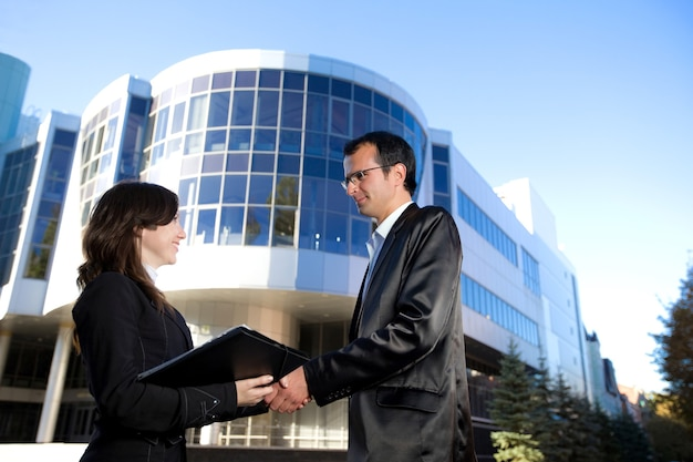 Uomo e donna in giacca e cravatta si stringono la mano stando in piedi davanti all'edificio per uffici