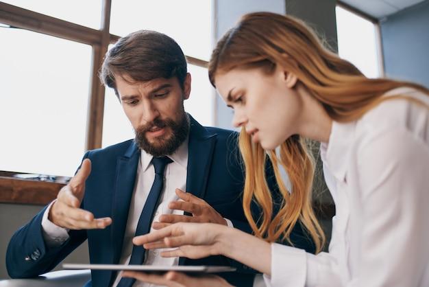 L'uomo e la donna in giacca e cravatta lavorano con un ufficio tecnologico per tablet