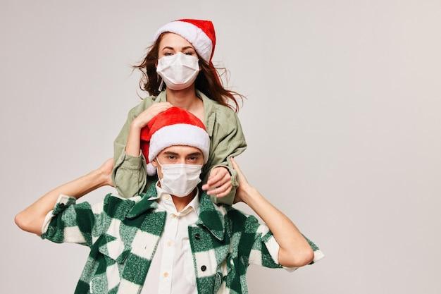 Un uomo e una donna festeggiano il natale indossando maschere mediche contro il coronavirus