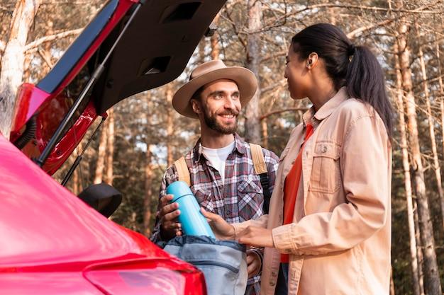 Uomo e donna in chat accanto alla loro auto