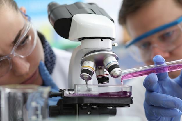 I chimici dell'uomo e della donna versano il liquido rosa dalla provetta per l'esame al microscopio