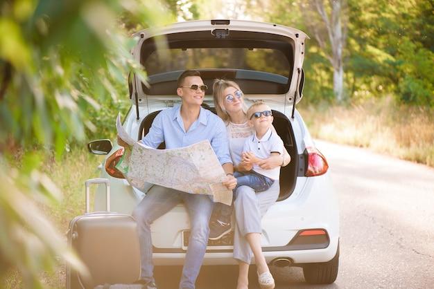 Un uomo una donna e un bambino di quattro anni nel bosco accanto alla macchina è pronto a viaggiare e scegliere un luogo sulla mappa dove andare ..
