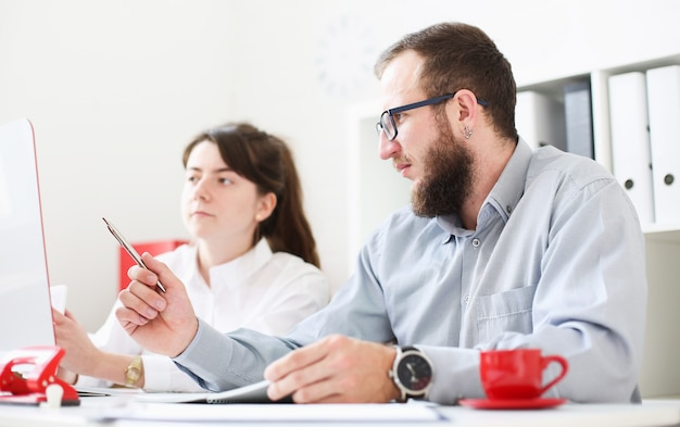 Uomo e donna che comandano un cabot in ufficio. l'uomo punta la penna verso il monitor