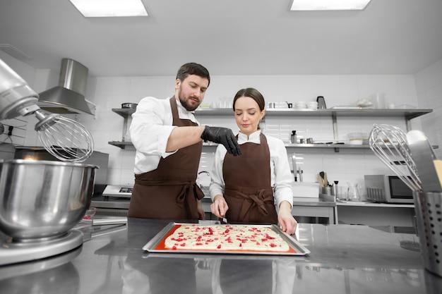 Un uomo e una donna cucinano in una cucina professionale e aggiungono frutti di bosco al pan di spagna