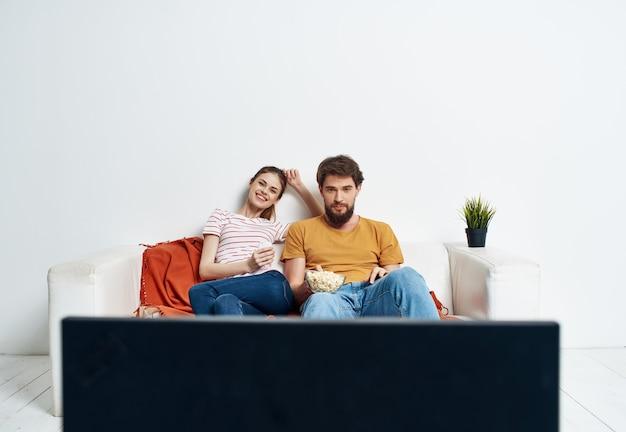 Uomo e donna sul divano che guardano un film intrattenimento per il tempo libero a casa