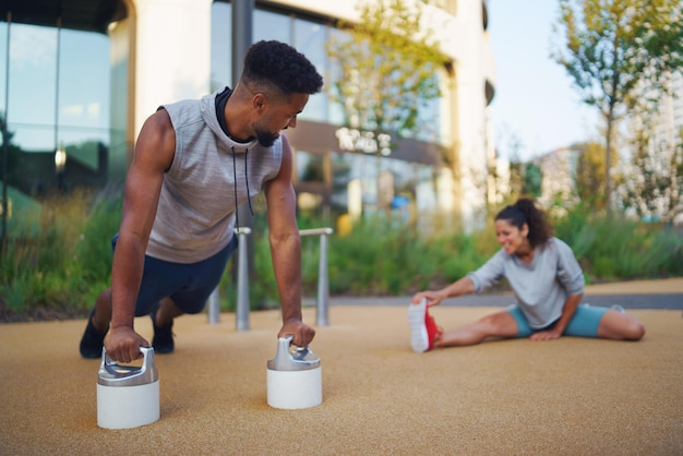 Uomo e donna coppia amici facendo esercizio di allenamento all'aperto in città, parlando.