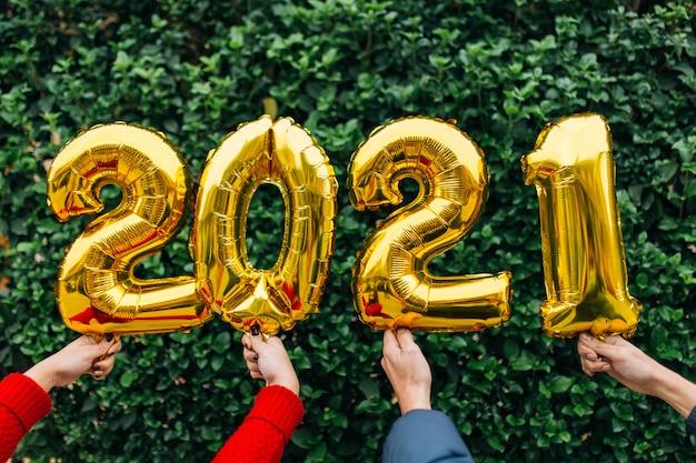 Mani di coppia uomo e donna che tengono palloncini in lamina d'oro numero 2021 davanti a un muro di piante. concetto di celebrazione del nuovo anno.