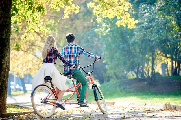Uomo e donna in bicicletta insieme in tandem doppia bici