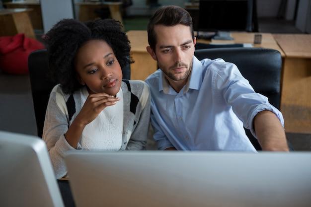 Uomo e donna che discutono su pc desktop