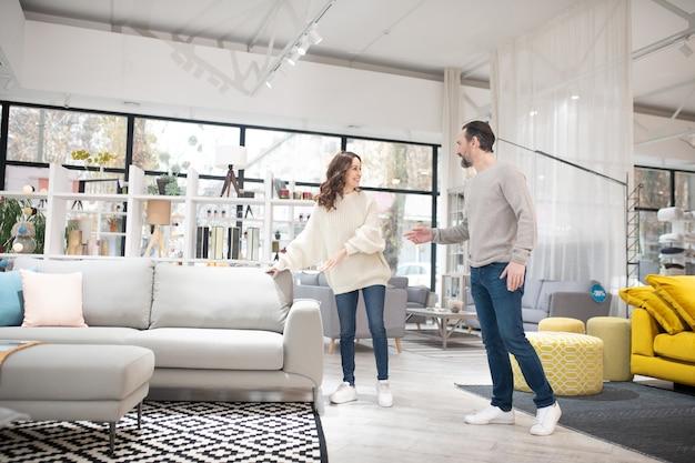 Uomo e donna che parlano di modelli di mobili in un moderno negozio di mobili