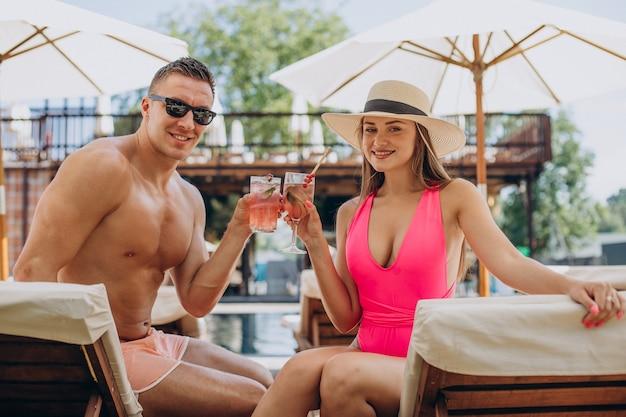 Uomo e donna che bevono cocktail a bordo piscina