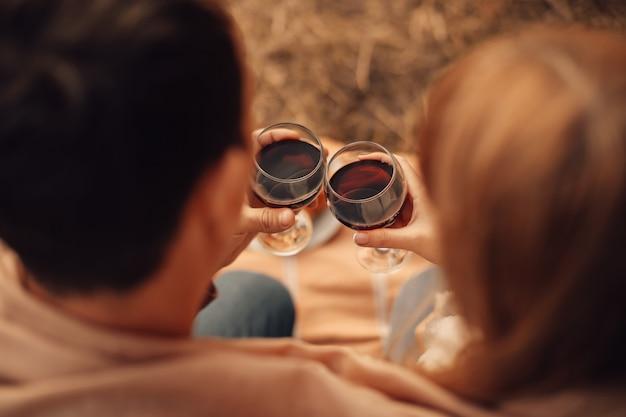 Uomo e donna che beve vino rosso, mani del primo piano con gli occhiali.