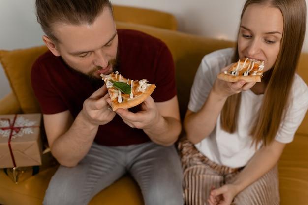 Uomo e donna che mangia pizza in un appuntamento a casa