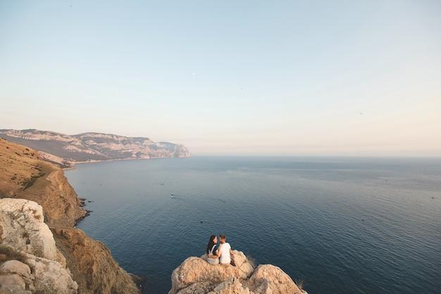 Uomo e donna sul bordo della scogliera contro le montagne e l'oceano