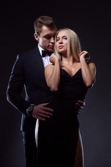 Un uomo e una donna in abiti eleganti si abbracciano appassionatamente godendosi questo momento