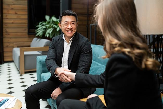 Un uomo e una donna terminano un incontro di lavoro si stringono la mano
