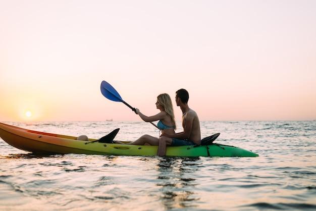 Uomo e donna che esplorano l'oceano in un kayak