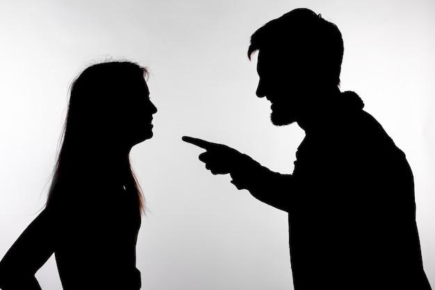 Uomo e donna faccia a faccia urlando gridando a vicenda silhouette di controversia isolato su sfondo bianco.