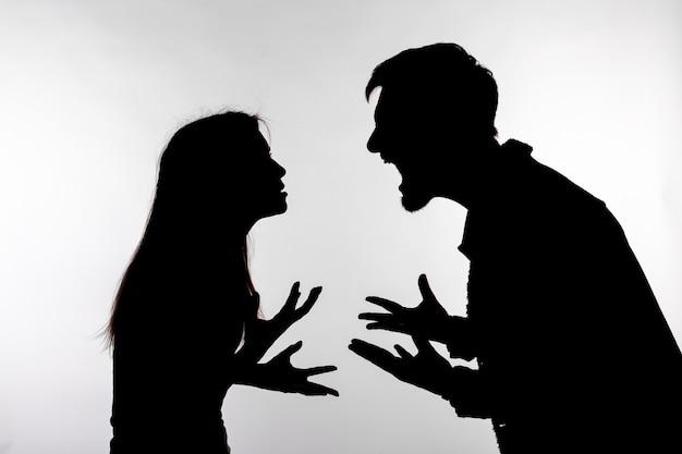Uomo e donna faccia a faccia urlando gridando a vicenda silhouette di controversia