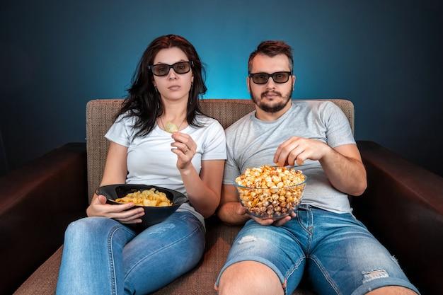 Un uomo e una donna, una famiglia che guarda un film o una serie in occhiali 3d, una parete blu. il concetto di cinema, film, emozioni, sorpresa, tempo libero, piattaforme di streaming.