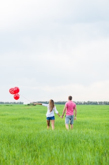 Uomo e donna sul campo con palloncini rossi. coppie felici sulla vista posteriore della natura