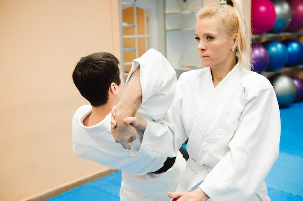 Uomo e donna che combattono all'addestramento dell'aikido nella scuola di arti marziali