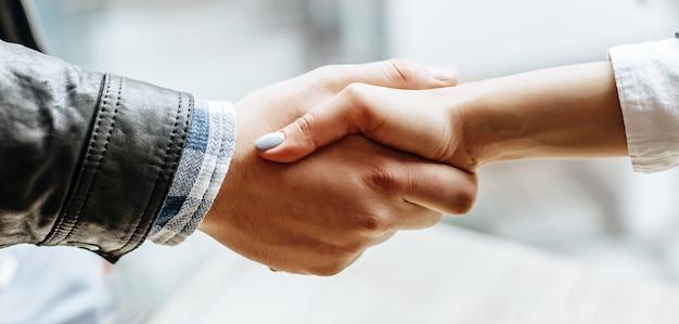 Agitazione della mano della donna e dell'uomo. stretta di mano dopo una buona cooperazione, imprenditrice stringe la mano con imprenditore professionista dopo aver discusso una buona dose di contratto. concetto di affari.