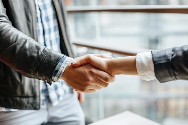 Tremante della mano della donna e dell'uomo. stretta di mano dopo una buona cooperazione, donna d'affari che stringe la mano a un uomo d'affari professionista dopo aver discusso di una buona quantità di contratto. concetto di affari.