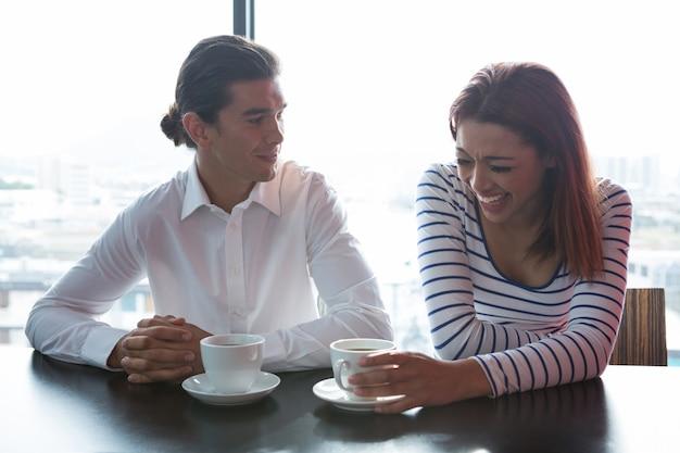 Uomo e donna che mangiano caffè