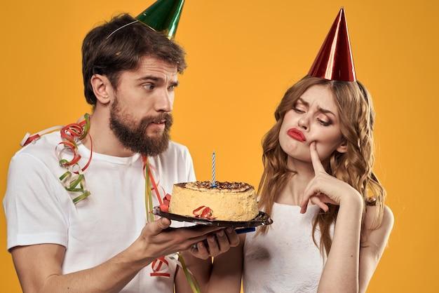 Uomo e donna che tengono una torta festiva di compleanno su priorità bassa gialla.