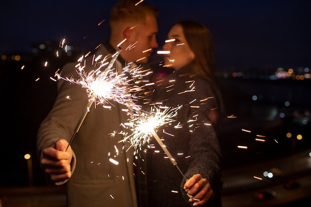 Uomo e donna che tengono una stella filante bruciante. fuoco del bengala