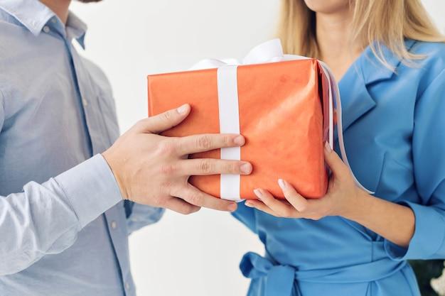 Uomo e donna con scatola regalo. festeggia un felice anno nuovo o natale