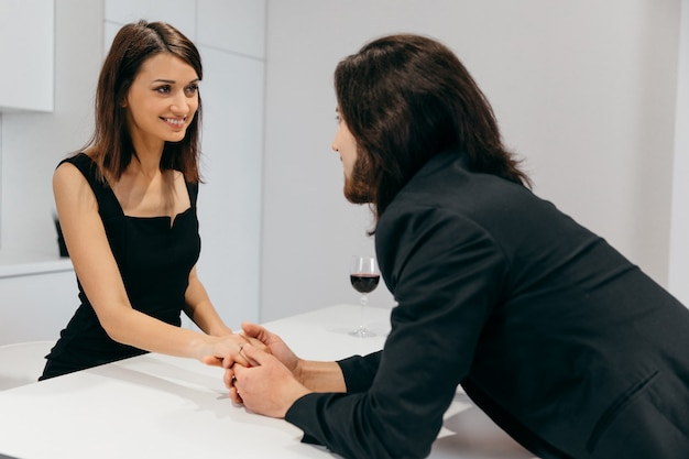 Uomo e donna che tengono le mani in un ambiente domestico romantico. foto di alta qualità