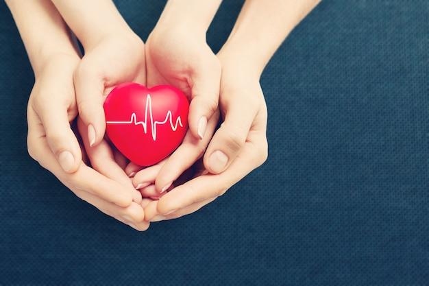 Uomo e donna che tengono il cuore rosso in mano su sfondo sfocato