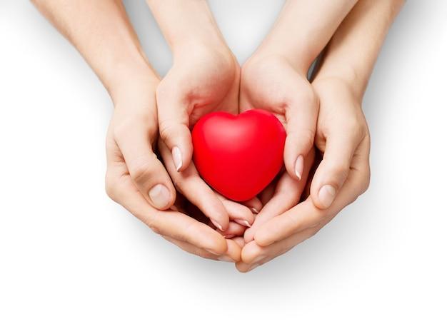 Uomo e donna che tengono il cuore rosso nelle mani isolate su bianco