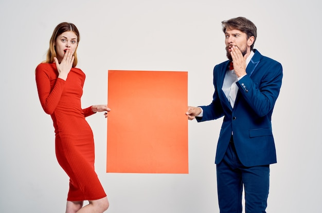 Uomo e donna che tengono il manifesto pubblicitario dello spazio della copia del modello rosso?