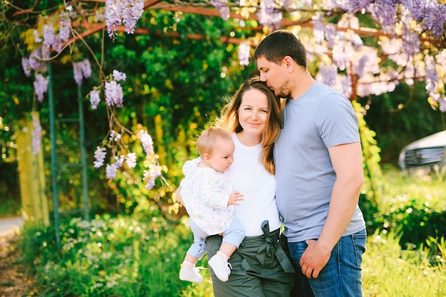 Uomo e donna che tengono la loro bambina sotto un albero di wysteria nel parco