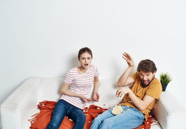Uomo e donna a casa sul divano a guardare la tv intrattenimento popcorn