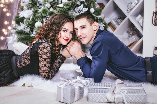 Uomo e donna a casa con decorazioni natalizie