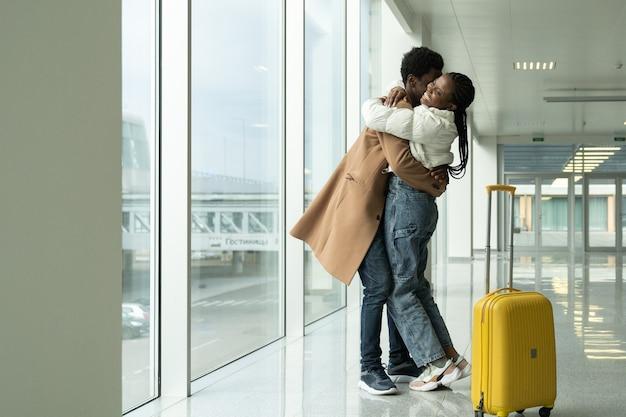 Uomo e donna che abbraccia all'aeroporto